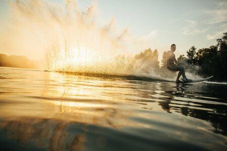 wakeboarding: Low angle shot of man wakeboarding on a lake. Man water skiing at sunset.