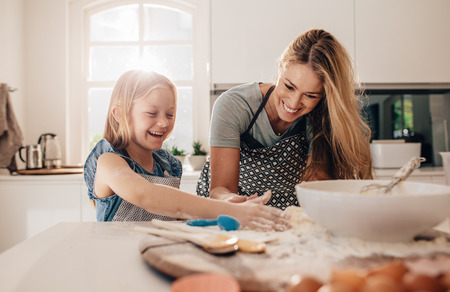 Happy young girl with her mother making dough. Mother and daughter baking in kitchen. Stock Photo