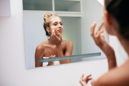 Young woman reflection in mirror applying cream in bathroom. Caucasian female doing beauty treatment on her face at home.
