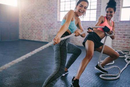 Shot of two young women doing exercises with rope at a gym. Fitness females pulling rope at gym. Stock Photo