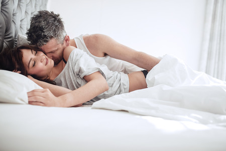 Intimate young couple enjoying sensual foreplay on bed. Man kissing on neck of woman. Stock Photo