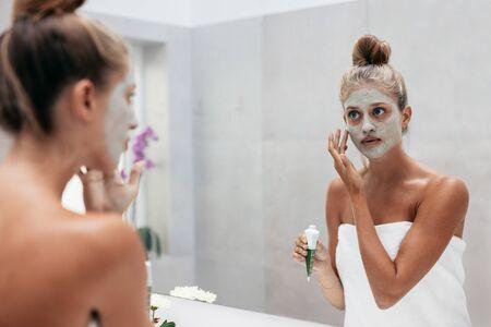 Mujer con máscara cosmética en la cara en el baño. Mujer joven que aplica la mascarilla delante del espejo.