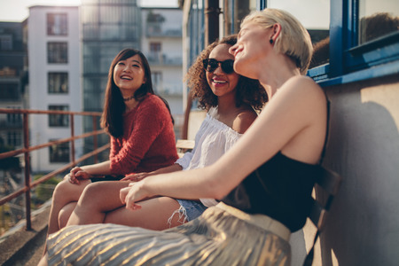 Three young female friends sitting in balcony and having fun. Women relaxing outdoors and chatting. Stock Photo