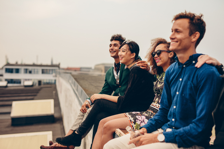 Shot of young men and women sitting together on rooftop. Mixed race friends relaxing on terrace. photo