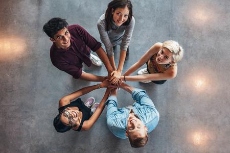 Groep gelukkige jonge studenten die eenheid. Bovenaanzicht van de multi-etnische groep jongeren zetten hun handen in elkaar. Jonge studenten staan in een cirkel maken stapel handen waaruit blijkt eenheid.