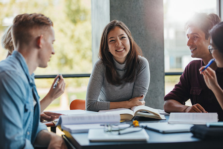 Sonriente joven sentado a la mesa con compañeros de clase en la biblioteca. Grupo de jóvenes estudiantes felices estudiando en la biblioteca.