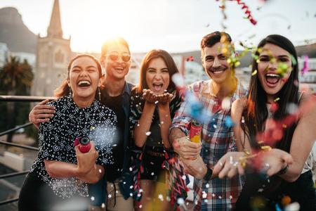 Groep vrienden genieten van de partij en het gooien van confetti. Vrienden plezier op het dak feest. Stockfoto