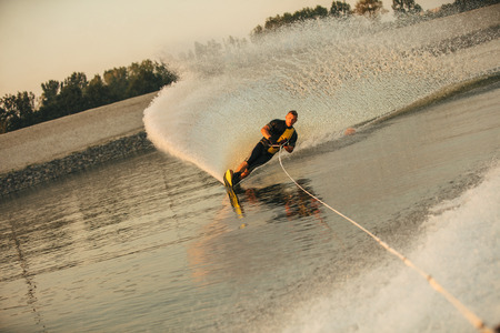 sportsperson: Wakeboarder surfing across the lake behind motorboat. Man water skiing on lake with water splashes.