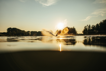 surface level: Water surface level shot of wakeboarder skiing on lake at sunset. Stock Photo
