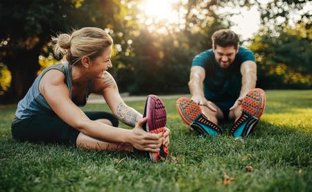 공원에서 스트레칭 행복 한 젊은 남자와 여자. 아침에 운동 백인 부부 웃 고.