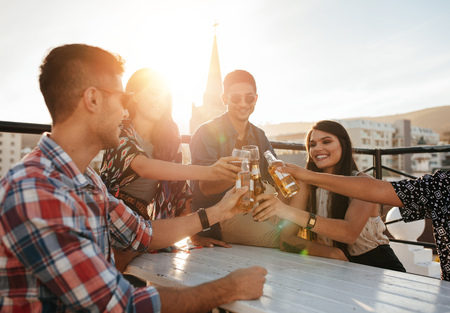 Happy young people toasting drinks at rooftop party. Young friends hanging out and enjoying with drinks. Stock Photo