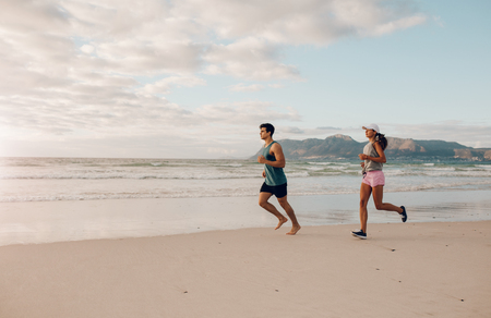 sportsperson: Full length shot of fit young man and woman running on the beach. Couple of runners on the sea shore.