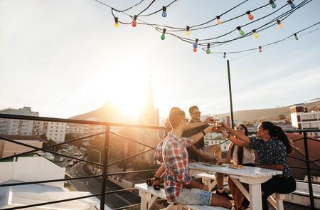 若者の屋外撮影の屋上パーティーで乾杯ドリンクを人します。若い友人が飲み物と一緒に出かけます。 写真素材
