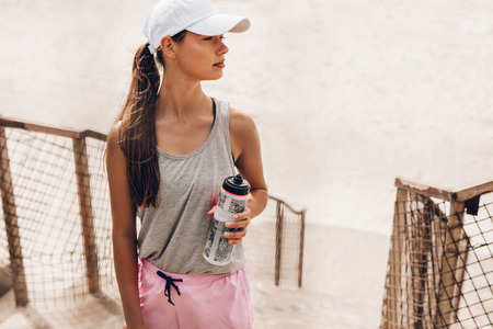 sportsperson: Shot of beautiful young woman at the beach taking a break. Fitness female with water bottle taking a break after workout. Stock Photo