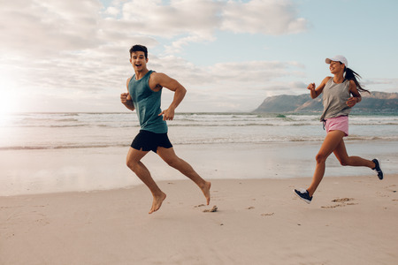 Full length shot of fit young man and woman running on the beach. Happy young couple of runners on the sea shore.