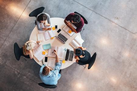 Bovenaanzicht van universitaire studenten zitten aan een tafel studeren en werken op de laptop