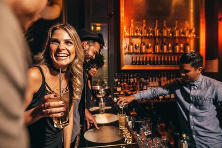 Mooie jonge vrouw met haar vrienden bij de bar. Jonge mensen genieten van een avond in club. Stockfoto