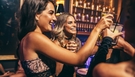 Group of young people celebrating at pub. Friends toasting cocktails in night club.