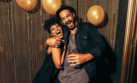Afbeelding van gelukkige jonge paar plezier op disco. Jonge man en vrouw genieten van een partij.