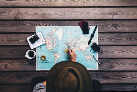 Турист, указывающий на Европу на карте мира, окруженный биноклем, компасом и прочими аксессуарами для путешествий. Человек в коричневой шляпе планирования своего тура, глядя на карту мира.