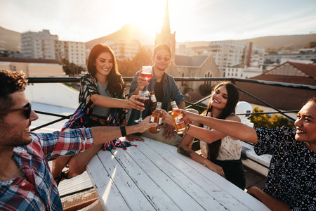 Multiracial young friends partying together. Group of people toasting drinks in a rooftop party.