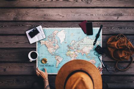 젊은 여자가 다른 여행 액세서리와 함께 세계지도 및 나침반을 사용하여 휴가 계획. 세계지도보고 갈색 모자를 착용하는 관광객. 스톡 콘텐츠