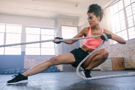 trineo: Disparo de la hembra joven de la aptitud que ejercita con la cuerda en un gym. Joven tirando de la cuerda en el gimnasio.