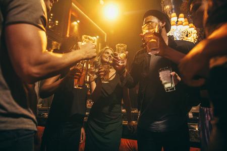 Groep vrienden die dranken hebben bij bar samen. Jongeren bij nachtclub die met cocktails genieten van.