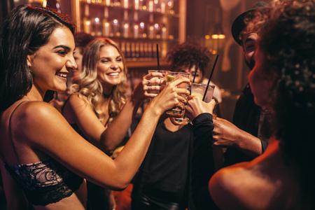Grupa młodych ludzi z koktajlami w nocnym klubie. Najlepsi przyjaciele imprezują w pubie i opiekują się drinkami.