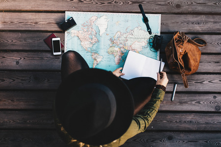 Top view of woman wearing hat making tour plan using a world map. Tourist exploring the world map with travel accessories around. Banco de Imagens