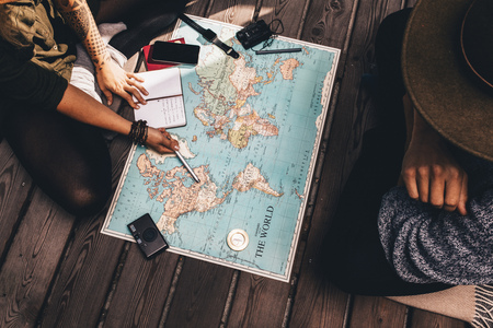 Man and woman discussing tour plans using the world map. Woman making notes and pointing on the map while the man is discussing. Stock Photo