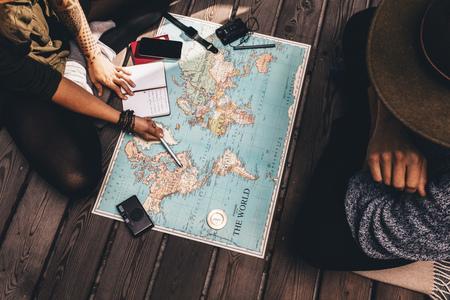 Muž a žena diskutovat o plánech zájezdu pomocí mapy světa. Žena dělá poznámky a ukazuje na mapu, zatímco muž diskutuje.