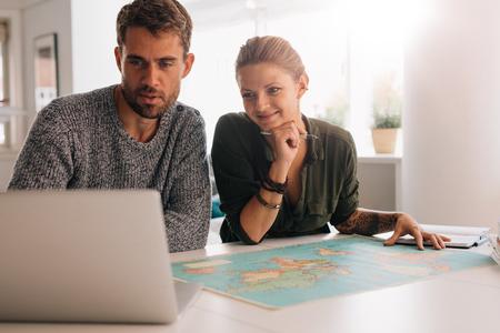 젊은 남자와 여자 세계지도 앞에 랩톱 컴퓨터를 찾고. 기술을 사용 하여 세계를 탐험하는 커플.