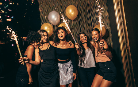 Group of women celebrating with fireworks at pub. Female friends enjoying party at nightclub.