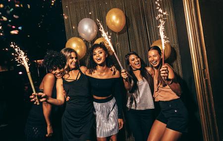 Gruppo di donne che celebrano con fuochi d'artificio al pub. femmina friends godendo festa in discoteca. Archivio Fotografico - 71712206