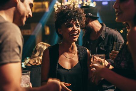 젊은 아프리카 여자 친구와 나이트 클럽에서 즐기는 쐈 어. 술집에서 좋은 시간을 보내고 사람들의 그룹입니다.