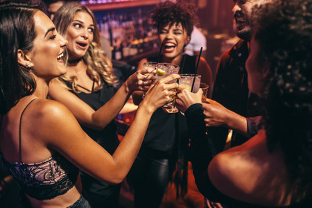 Grupo de amigos de fiesta en un club nocturno y bebidas tostado. Felices los jóvenes con un cóctel en el bar.