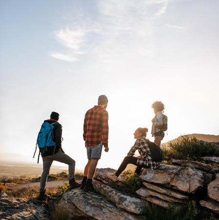 お友達とリラックスの田園地帯で岩の上。若者のハイキング。