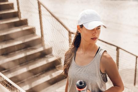 ビーチ開催水のボトルに立って、離れて見て帽子の美しい若い女性のショット。フィットネス女性ワークアウト後休憩します。 写真素材