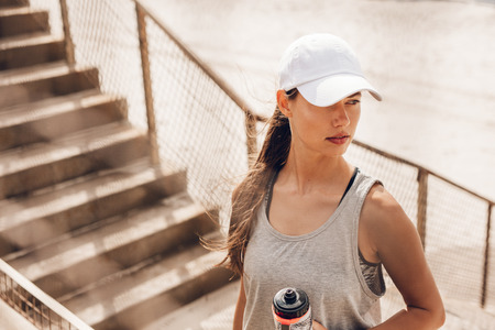 sportsperson: Shot of beautiful young woman in hat standing at the beach holding water bottle and looking away. Fitness female taking a break after workout.