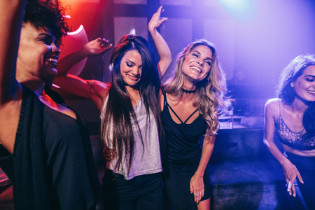 Shot of happy young people having fun at disco. Female friends dancing together in nightclub. Archivio Fotografico