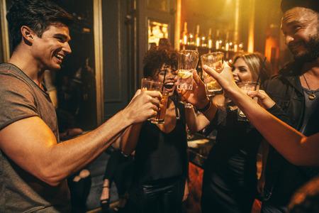 Groep mannen en vrouwen genieten van drankjes in de nachtclub. Jonge mensen bij bar roosteren cocktails en lachen.