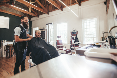 haircut: Hairdresser with client sitting at salon and smiling. Man getting haircut at barber shop. Stock Photo