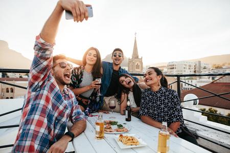 Groep vrienden nemen selfie op een slimme telefoon. Jonge mensen op het dak partij nemen selfie. Stockfoto
