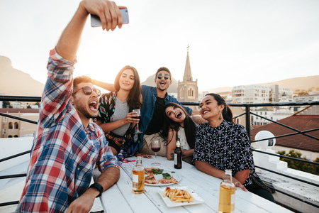 Grupo de amigos que toman selfie en un teléfono elegante. Jóvenes en el partido de la azotea tomando selfie.