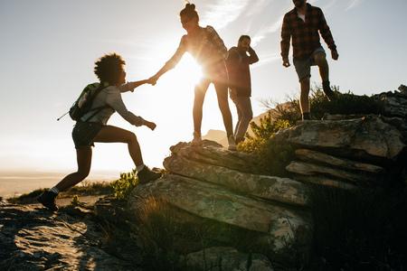 Skupina turistů na hoře. Žena pomáhá svému příteli vylézt na skálu. Mladí lidé na horské túru při západu slunce.