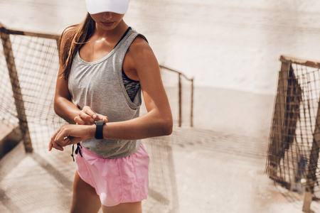 Young woman setting fitness app before workout. Female runner using smart watch to monitor her performance. Imagens
