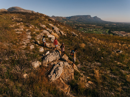 extreme terrain: Aerial view of young people through extreme terrain in countryside. Group of friends hiking in mountains. Stock Photo