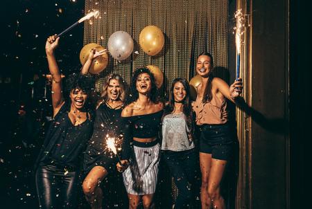 Geschotene beste vrienden die de vooravond van de nieuwe jaar holdingssterretjes vieren in een partij. Groep vrouwen die partij hebben bij nachtclub.