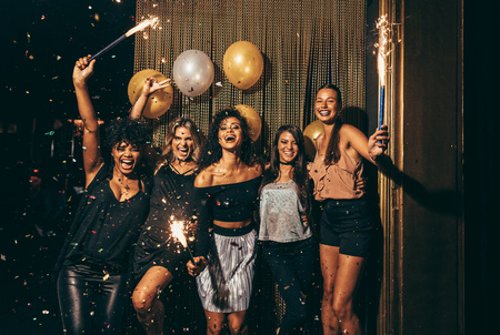 Shot best friends celebrating new years eve holding sparklers in a party. Group of women having party at nightclub. Stock Photo